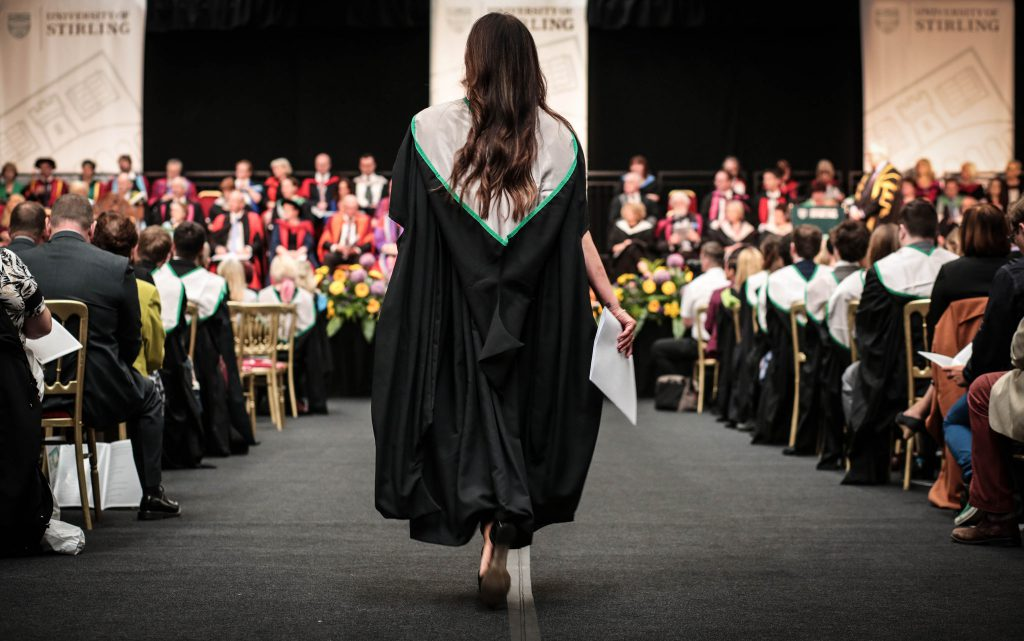 Woman walking down aisle after Graduation at University of Stirling